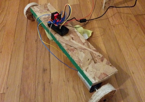 Two wheels and motors bolted to a piece of OSB, held up by a rag, with a circuit board attached via rubber band and wires extending off frame